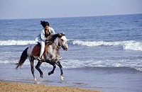 Young woman riding horse along beach