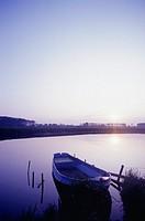 Boat on lake shore at dusk