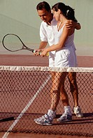 Young man teaching young woman to play tennis