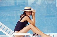 Young woman sitting on sunlounger by pool, portrait