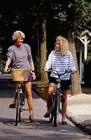 Two mature women sitting on bicycles in avenue