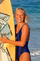Young woman with surfboard on beach, front view