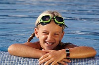 Head and shoulders of girl leaning on edge of swimming pool wearing goggles on her forehead, smiling, portrait