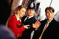 Businesspeople on street talking to London policeman, (Close-up)