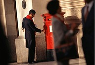 Businessman mailing letter at post box in street