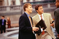 Businessmen having discussion in street