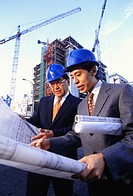 Architects discussing blueprints at construction site