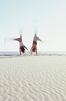 Two young women cartwheeling on beach, defocused