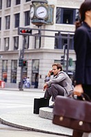 Businessman sitting on city street talking on cell phone