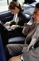 Businessman and businesswoman in taxi