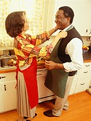 Wife adjusting apron of husband in kitchen