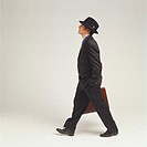 Businessman with hat and briefcase, walking