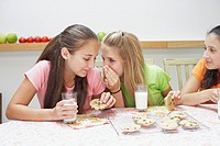 Three teenage girls eating cookies with milk on a dining table