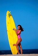 Woman in swimsuit holding surfboard