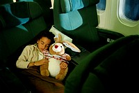 Girl sleeping with stuffed animal in commercial airplane