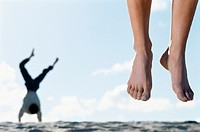 Man doing handstand focus on woman´s foot