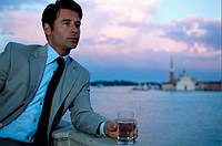 Businessman leaning on bridge, looking away