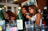 Couple holding drinks in beer bar, outdoors