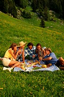 Group of people having picnic, sitting on grass