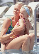 Mother sitting with daughter (2-3) in outdoor swimming pool, portrait