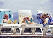 Three children lying on lounge chairs by swimming pool
