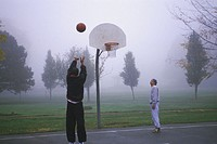Two young men playing basketball on street court