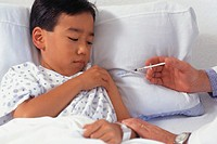 Doctor in hospital giving boy (5-6) injection in arm
