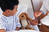Boy (6-7) in bed watching doctor give injection to arm of toy animal