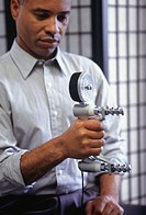 Man holding dynamometer in right hand