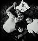 Father and three children (4-8) lying on grass, overhead view (B&W)