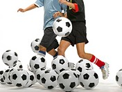 Two kids kicking footballs