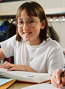 portrait of a young girl with glasses as she sits and smiles at her desk in her classroom