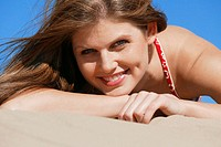 a young attractive caucasian female lays at the beach and smiles