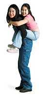 silhouette of an asian teenage girl in denim overalls as she gives her little sister a piggy back ride