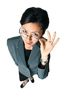 an adult asian business woman in a grey suit holds her glasses and glances up at the camera