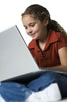 medium shot of a female child as she sits and works on a laptop computer