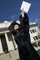 medium shot of a young adult female in her cap and gown as she celebrates her graduation