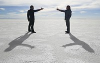 conceptual shot of two business people as they stand in an open desert and point at each other