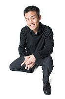 a young asian man dressed in black crouches down smiles