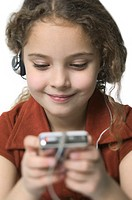 close up shot of a young female child as she listens to music on a mp3 player