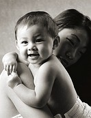 black and white photograph of a young asian  mother playing with her baby as it flashes a smile