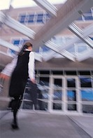 A BUSINESSWOMAN IN A WHITE SHIRT AND BLACK DRESS CARRIES A BRIEF CASE AS SHE WALKS TO A WINDOWED BUILDING