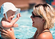 young blonde mother plays in the pool with her infant