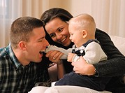 happy young parents play with their new baby in their livingroom