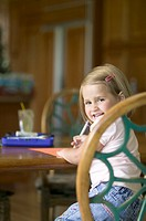 lifestyle portrait of a female child drawing at a table as she turns and smiles