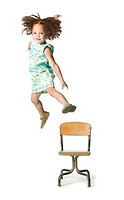 full body shot of a female child as she jumps off a chair and flies through the air