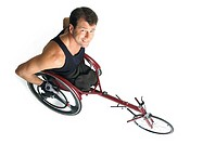 an adult caucasian male wheelchair racer in a black tank top smiles as he looks up at the camera