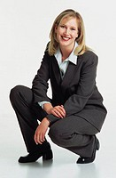 a beautiful young caucasian woman with shoulder length blond hair in a dark grey business suit in a crouched position looking into the camera