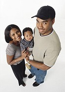 young african american couple smile and hold infant between them