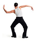 a young caucasian male dancer in black pants and white tank top stretches out and moves his arms with his back to the camera